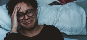 sad man sitting against a bed