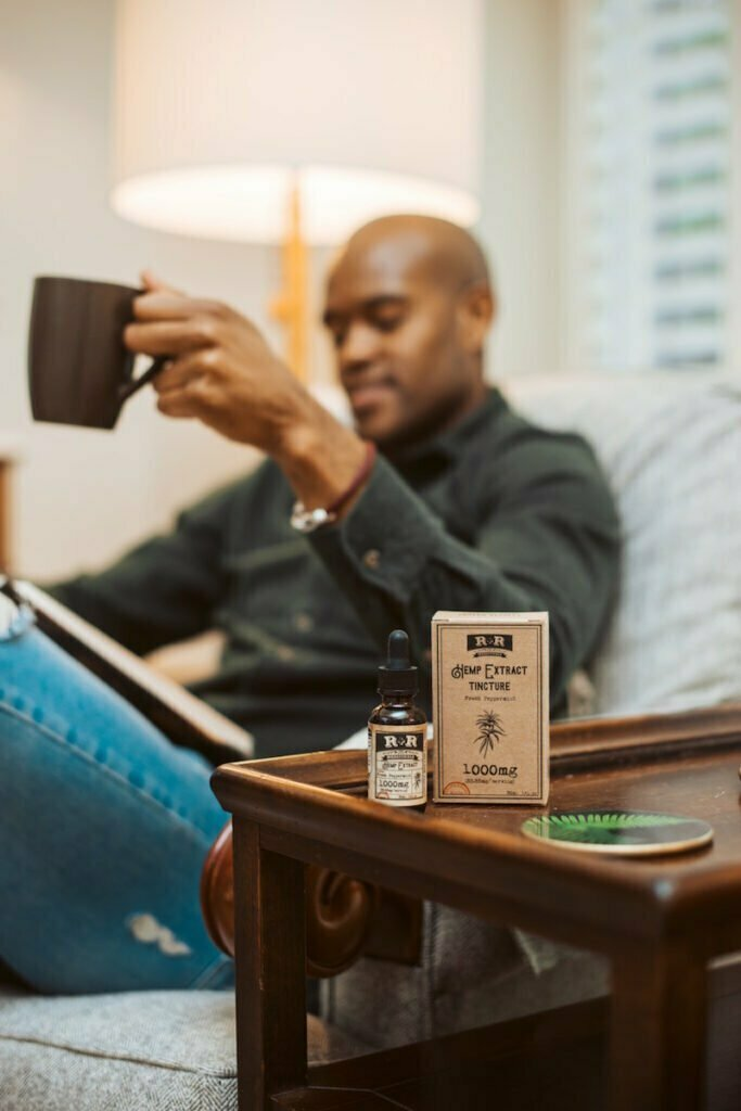cbd oil and bottle in front of man drinking coffee
